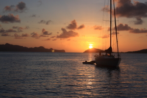 Sailing yacht at anchor in the Grenadines with the sunset behind.